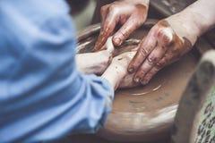 Traînez en enseignant une fille à faire le pot d'argile sur la roue du ` s de potier images stock