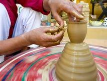 Traînez en faisant le pot d'argile sur une roue colorée images stock