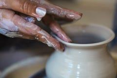 Traînez en moulant une forme dans le pot avec des doigts, mains hautes de potier de fin, modifiées la tonalité photos libres de droits