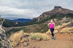 Traînez la fille courante en montagnes sur le sentier piéton rocheux photo libre de droits