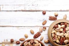 Traînez le mélange avec différents genres d'écrous dans la cuvette en bois brune sur le fond en bois blanc rayé de table, lumière photo stock
