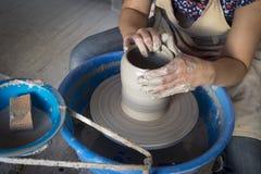 Traînez les mains du ` s faisant un pot d'argile sur la poterie images libres de droits