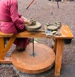 Traînez les mains faisant en argile sur la roue de poterie Le potier effectue sur le bac d'argile de roue de poterie photographie stock