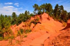 Traînez par les falaises ocres rouges près de Rousillon, Provence, France photo stock