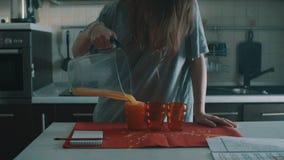 Traag donkerbruin meisjes gietend jus d'orange in rood glas, morserijen het overal stock video
