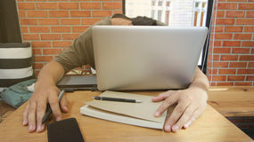 Trabaja independientemente el trabajador asiático del hombre que duerme en el ordenador portátil con el cuaderno, smar fotos de archivo