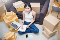 Trabaja independientemente la mujer asiática que trabaja con concepto de la caja en casa Imagen de archivo