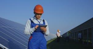 Trabajador étnico en el casco de protección usando la tableta entre los paneles solares almacen de metraje de vídeo
