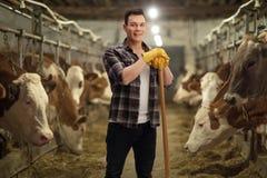 Trabajador agrícola joven que presenta en un establo fotos de archivo libres de regalías