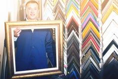Trabajador alegre que lleva a cabo moldear que enmarca de la imagen de madera Imágenes de archivo libres de regalías