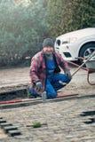 Trabajador alegre que pone pavimentando ladrillos en invierno Fotografía de archivo libre de regalías