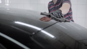 Trabajador anónimo que limpia la ventana de la máquina con el trapo metrajes