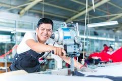 Trabajador asiático que usa una máquina en una fábrica fotos de archivo