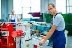 Trabajador blanco joven en fábrica usando la máquina Fotos de archivo libres de regalías