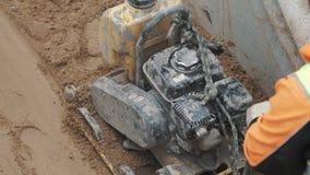 Trabajador a cámara lenta que usa el compresor de la placa de la gasolina en la arena en zanja en el solar almacen de metraje de vídeo