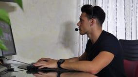 Trabajador casero de sexo masculino joven con las auriculares almacen de video