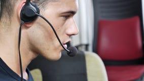 Trabajador casero de sexo masculino joven con las auriculares almacen de metraje de vídeo