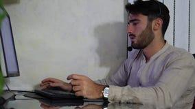 Trabajador casero de sexo masculino joven con las auriculares metrajes