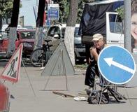 Trabajador cerca de una portilla abierta y rodeado por las señales de tráfico Fotos de archivo libres de regalías