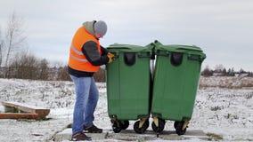 Trabajador cerca del envase de la basura almacen de metraje de vídeo