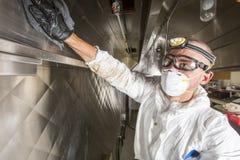 Trabajador comercial de la cocina que se lava para arriba en el fregadero en cocina profesional fotos de archivo
