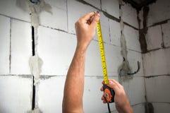 Trabajador con cinta métrica en centímetros y pies Fotografía de archivo