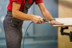 Trabajador con el arma de pegamento y tablero en el taller Imagenes de archivo