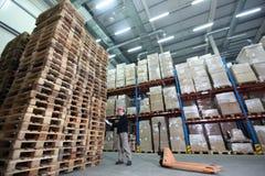 Trabajador con el camión de plataforma de la mano en la pila grande de plataformas de madera en almacén Foto de archivo