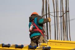 Trabajador con el cinturón de seguridad y casco en el área de la reconstrucción Foto de archivo libre de regalías