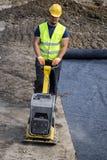 Trabajador con el compresor de la placa vibrante Foto de archivo