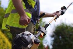 Trabajador con el condensador de ajuste de seto Fotos de archivo libres de regalías