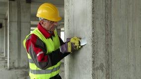 Trabajador con el cuchillo de masilla en el emplazamiento de la obra almacen de video