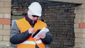 Trabajador con el edificio inacabado de la tableta y de la documentación almacen de video