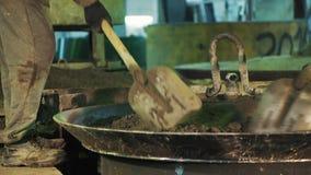 Trabajador con el empuje de la pala que sacude partículas del cemento en la tapa de la caldera del metal almacen de metraje de vídeo