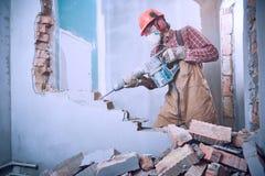 Trabajador con el martillo de la demolición que rompe la pared interior Foto de archivo libre de regalías