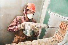 Trabajador con el martillo de la demolición que rompe la pared interior Fotografía de archivo libre de regalías