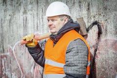 Trabajador con el martillo de trineo cerca de la pared Imágenes de archivo libres de regalías