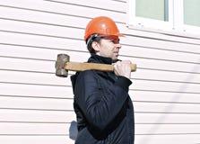 Trabajador con el martillo de trineo grande en el hombro Imágenes de archivo libres de regalías