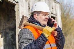 Trabajador con el martillo de trineo que habla en el teléfono celular Imagen de archivo libre de regalías