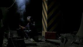 Trabajador con el metal de soldadura de la máscara protectora soldadura en fondo negro en la cámara lenta Hombre con la soldadura metrajes