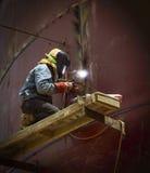 Trabajador con el metal y las chispas de soldadura de la máscara protectora Fotografía de archivo libre de regalías