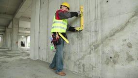 Trabajador con el nivel amarillo en el solar almacen de metraje de vídeo