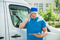 Trabajador con el teléfono móvil y la tableta de Digitaces Imágenes de archivo libres de regalías