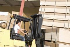 Trabajador con la carretilla elevadora que apila la madera imagen de archivo libre de regalías