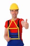 Trabajador con la casa y el pulgar plegables del criterio para arriba Fotos de archivo libres de regalías