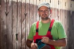 Trabajador con la chorreadora vibrante que se coloca delante de pantano de madera viejo Imagenes de archivo
