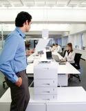 Trabajador con la máquina de la copia en oficina Imagen de archivo libre de regalías
