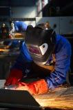 Trabajador con la máscara protectora y los guantes grinding/we Foto de archivo