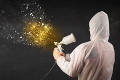 Trabajador con la pintura del aerógrafo con la pintura de oro que brilla intensamente Foto de archivo