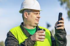 Trabajador con la taza de café y de teléfono celular Imagenes de archivo